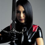 Young woman in leather top posing with sword